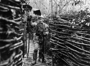 1916: A French soldier standing in a trench wearing a gas mask and makeshift winter uniform. (Photo by Henry Guttmann/Getty Images)